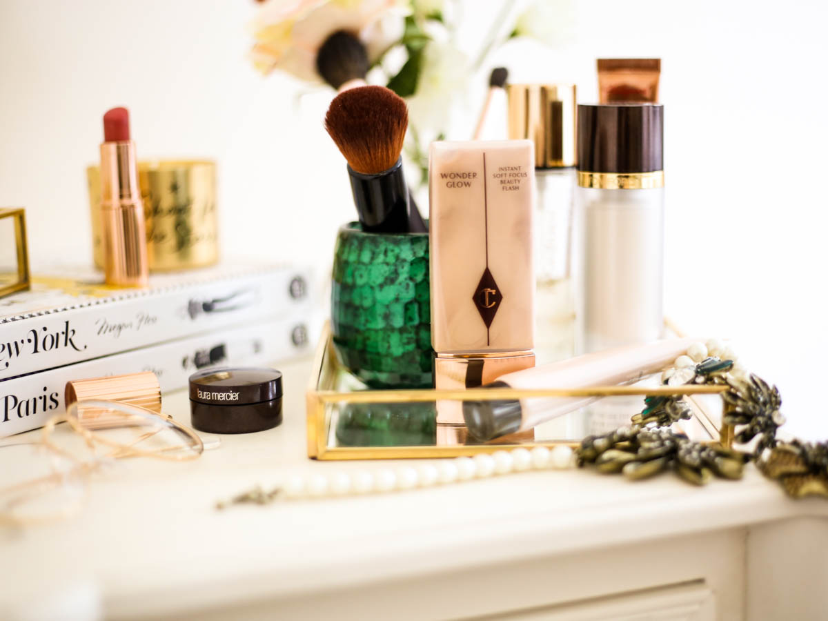 Get the glow favourites for glowing skin | dressing table setting with glow primers feat charlotte Tilbury wonder Glow makeup brush holder and Megan Hess books