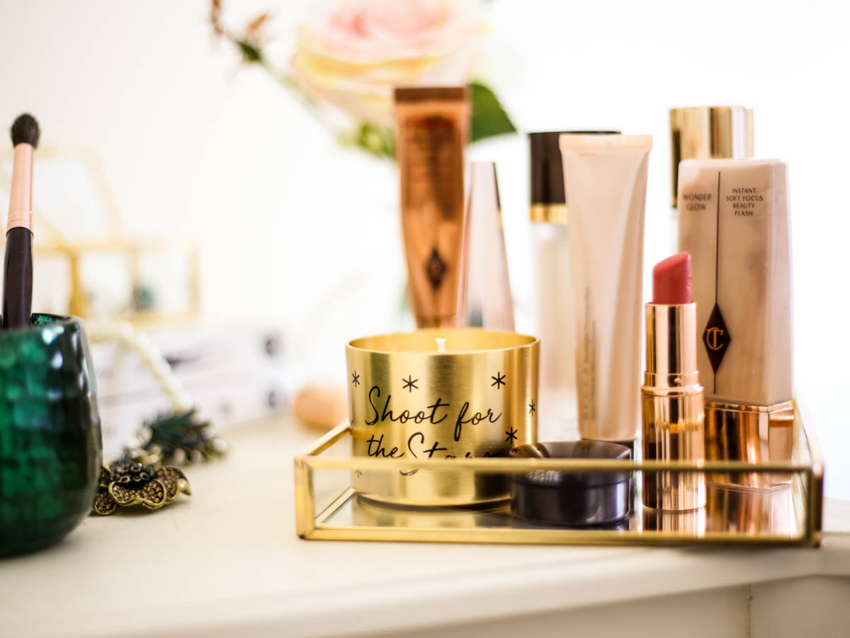 Get the glow favourites for glowing skin | glow primer feat Charlotte Tilbury Matte Revolution Lipstick, gold candle and brush holder on dressing table