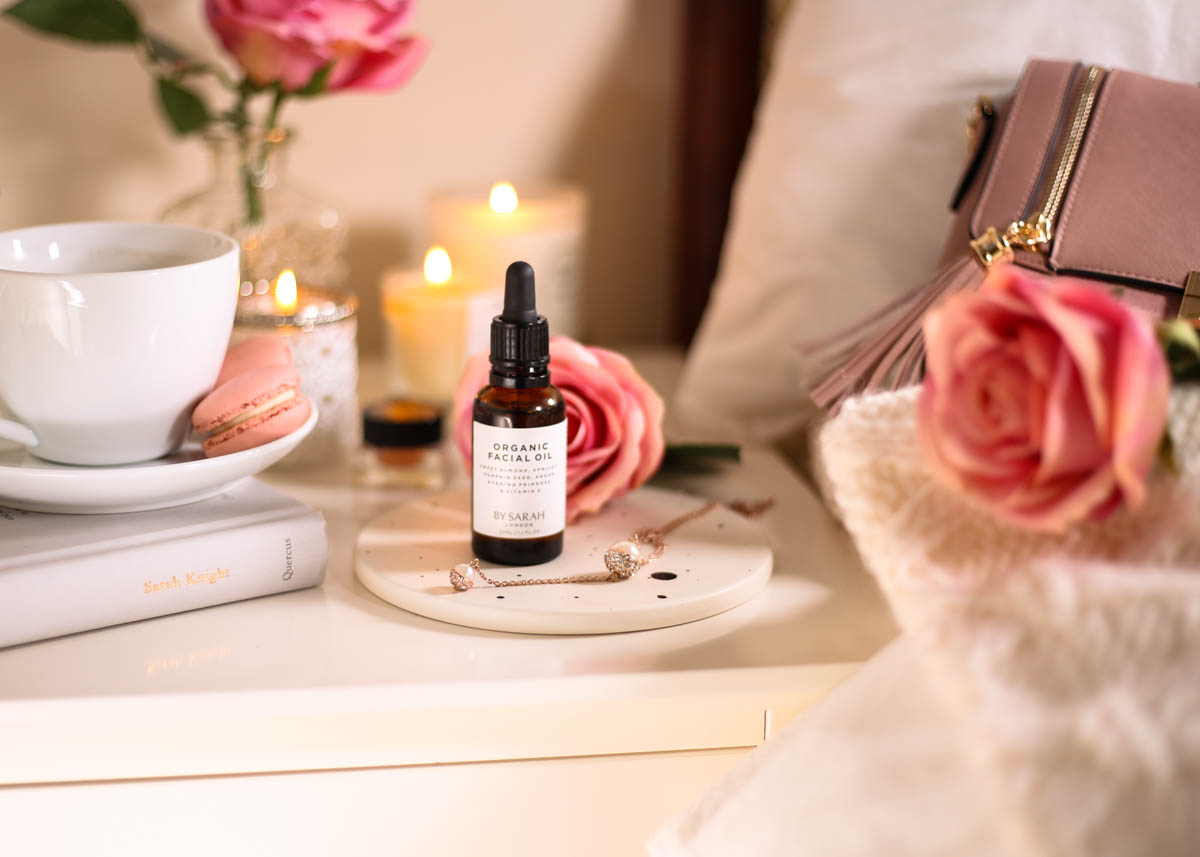 The Organic Facial Oil You Need to Know About- By Sarah London Organic Facial Oil on bedside table with book and macaron