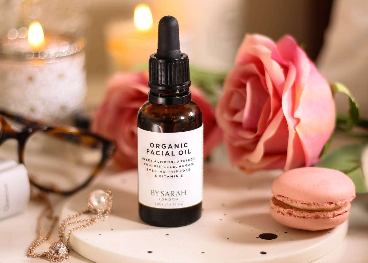 The Organic Facial Oil You Need to Know About- By Sarah London Organic Facial Oil styled on bedside table with book, glasses, macaron, roses & necklace
