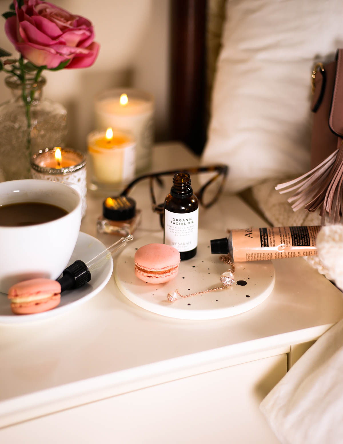 The Organic Facial Oil You Need to Know About- By Sarah London Organic Facial Oil with pipette. Styled with book coffee mug, macaron & candles