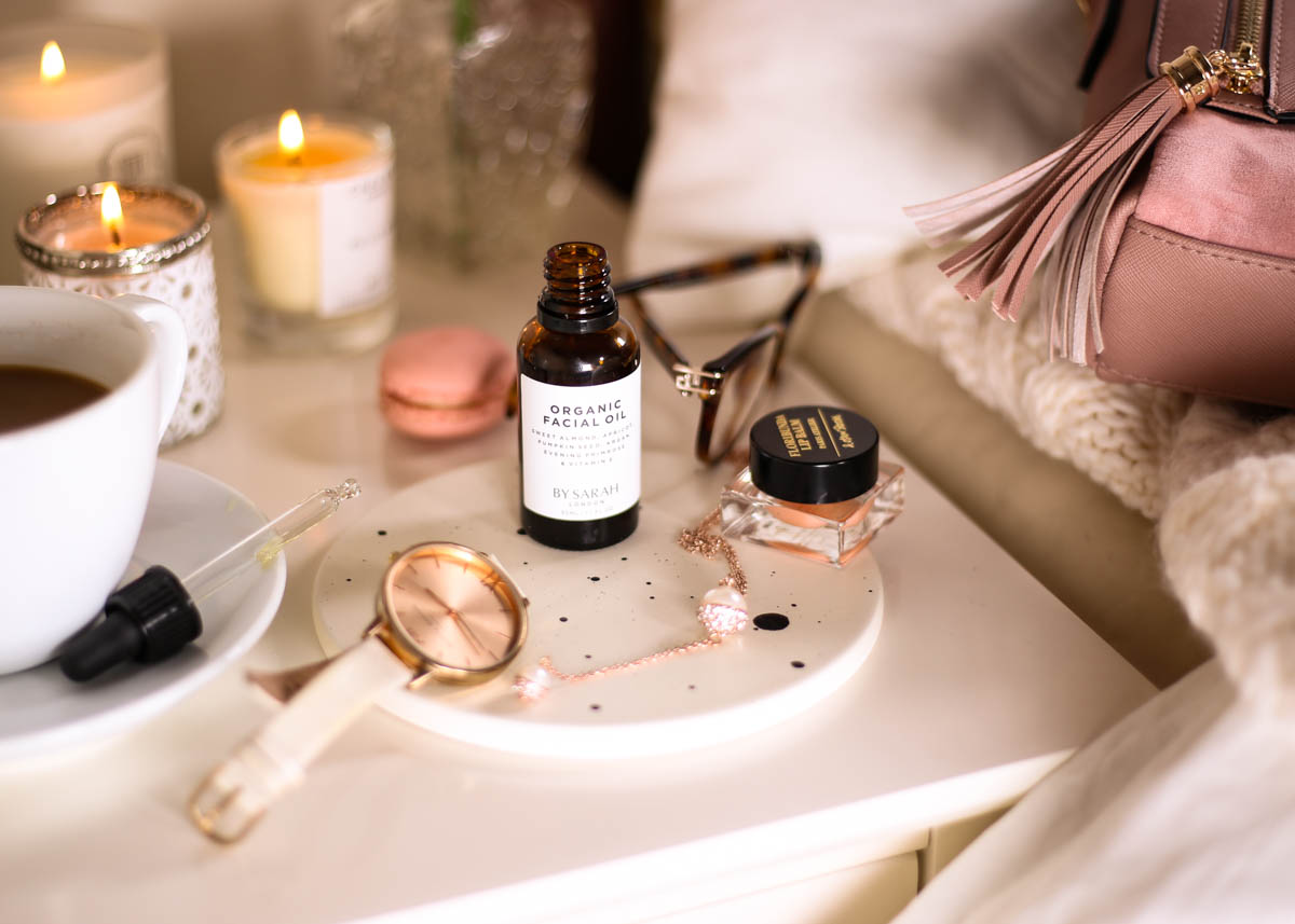 The Organic Facial Oil You Need to Know About- By Sarah London Organic Facial Oil wth pipette styled on bedside table with lip balm, watch, candles and bag