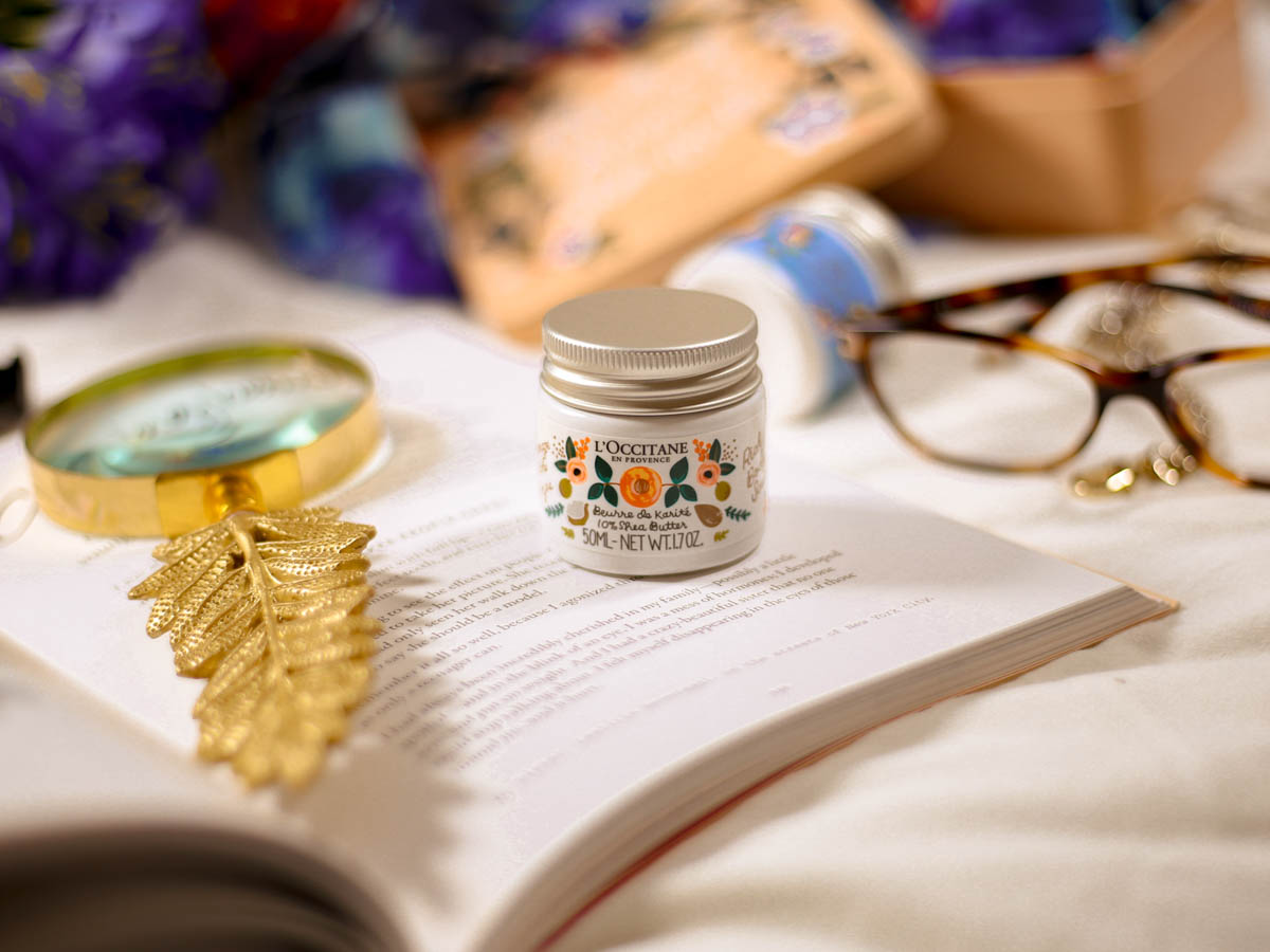 New Beauty Highlights | L'Occitane x Rifle Paper Co Design Shea Ultra Rich Body Scrub styled on bed with book and glasses