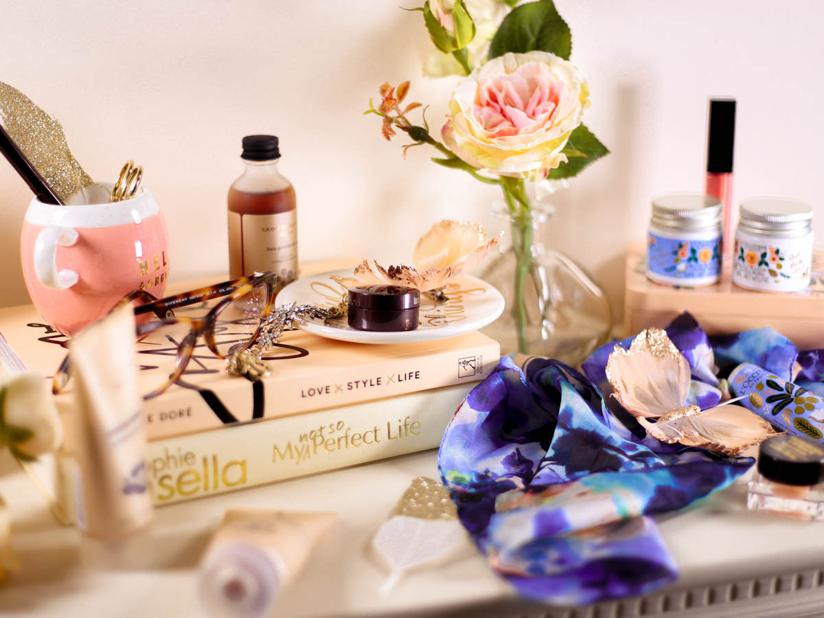 New Beauty Highlights | Makeup & bodycare and beauty items on dressing table with fashion scarf & book
