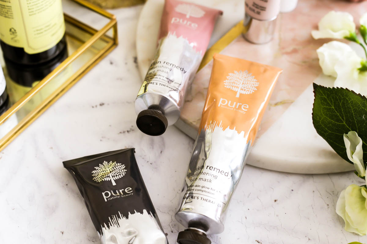 3 Amazing Face Masks from Pure's New Skin Remedy Range | feat close up of Pure Deep Cleansing Mask, Pure Nourishing Face Mask & Pure Brightening Face Mask against round marble board & flowers