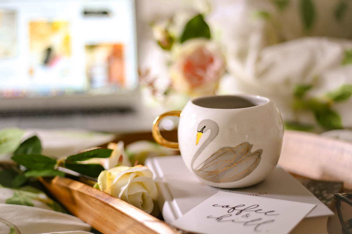 Essential Tips for Growing Your Blog | feat close up of swan mug on book on bed with laptop