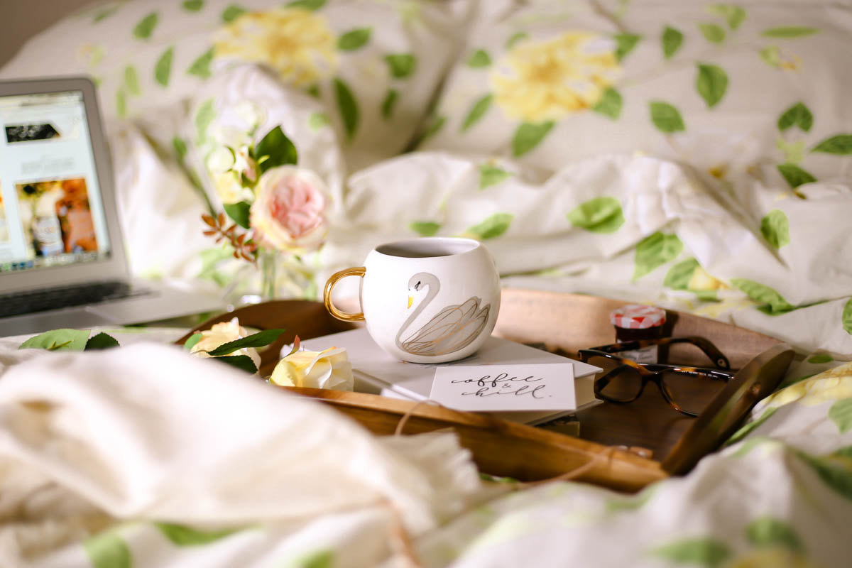 Essential Tips for Growing Your Blog | feat swan mug on book on bed with laptop