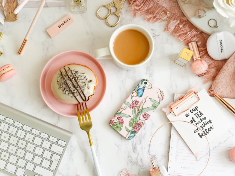 My Workday Essentials | feat Caseapp Parrot & Flowers iPhone Case on desktop setting with tea & doughnut & clipboard