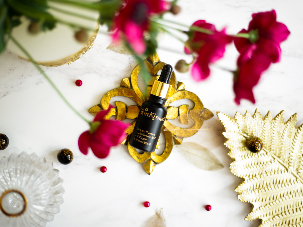 Reviewing the Skinkissed Vitamin C Serum   styled on coaster with flowers_