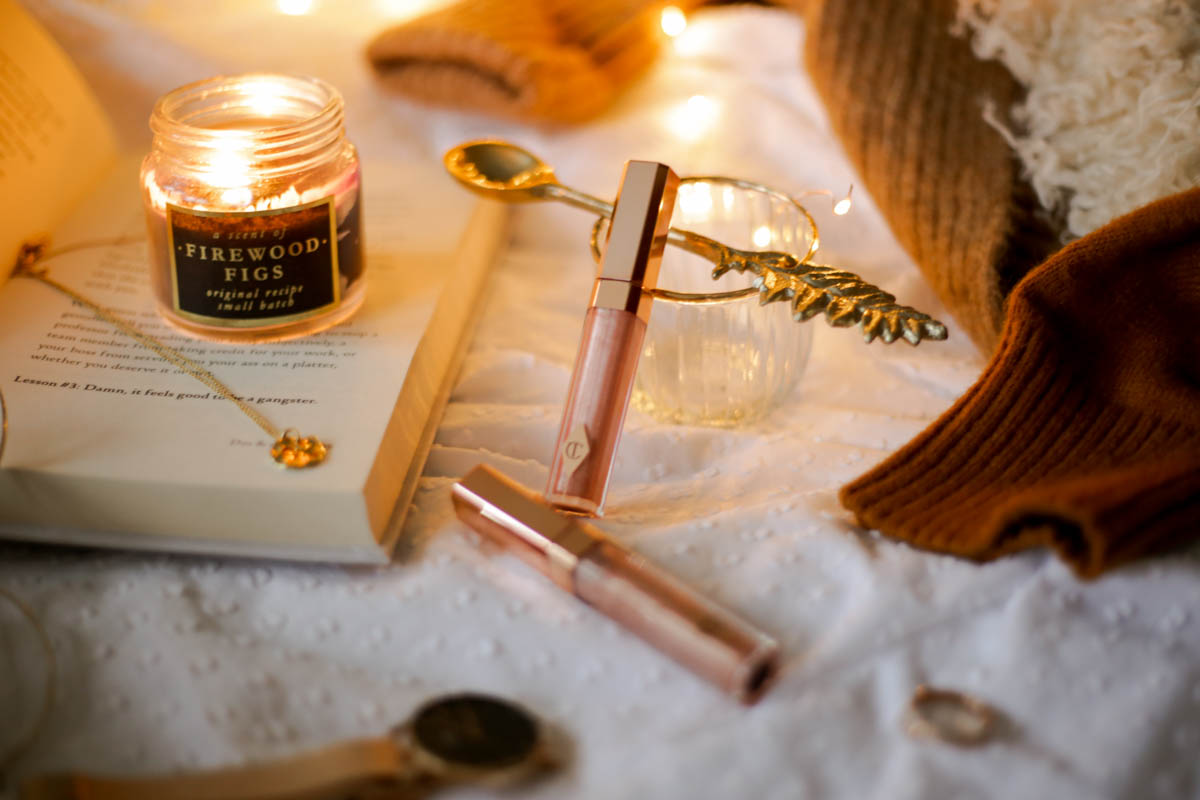 Three Favourite Lip Glosses- Charlotte Tilbury Lip Lustre in Blondie and Ibiza Nights styled with candle on book
